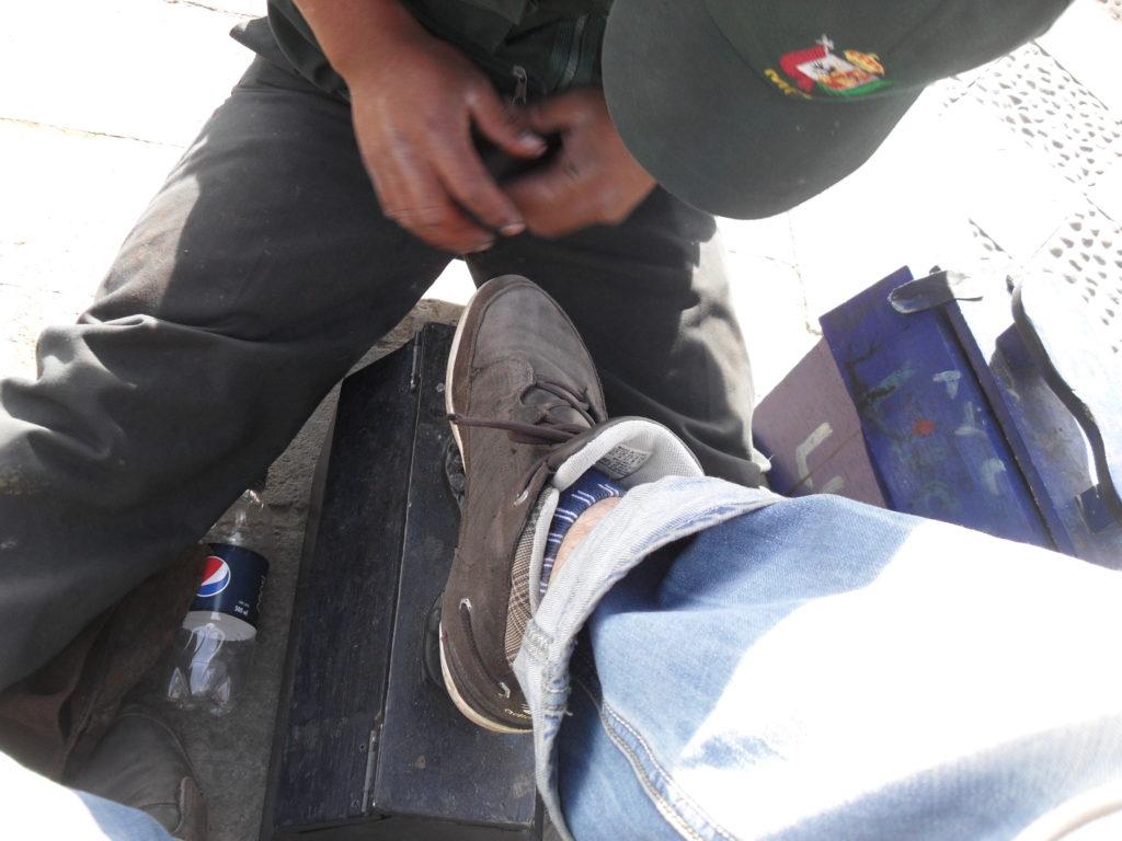 Ein junger Mann putzt mir an der Plaza de Armas von Cajamarca für 5 Soles die Schuhe